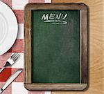 Menu blackboard lying on table with plate, knife and fork Stock Photo - Royalty-Free, Artist: andrey_kuzmin                 , Code: 400-06562215