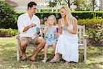 A young family mother & father parents with girl child blowing bubbles having fun together sitting on a bench in a sunny park or garden. Stock Photo - Royalty-Free, Artist: darrenbaker                   , Code: 400-06562527