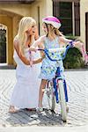 Young girl child riding a bicycle with her happy excited mother parent giving encouragement alongside her Stock Photo - Royalty-Free, Artist: darrenbaker                   , Code: 400-06562528