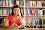 Portrait of cute girl with open book looking at camera in college library Stock Photo - Royalty-Free, Artist: pressmaster                   , Code: 400-06564502