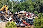 A pile of wrecked cars and auto bodies are crushed and stacked for spare parts or metal salvage.  Trees and weeds surround pile. Stock Photo - Royalty-Free, Artist: bonniemarie                   , Code: 400-06565955