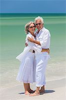 Happy senior man and woman couple together embracing by sea on a deserted tropical beach with bright clear blue sky Stock Photo - Royalty-Freenull, Code: 400-06566223