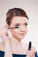 Head and Shoulders Portrait of Teenage Girl Putting on Mascara in Studio Stock Photo - Premium Royalty-Freenull, Code: 600-06570933