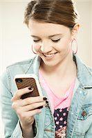 Portrait of Teenage Girl Reading Text Message on a Cell Phone in Studio Stock Photo - Premium Royalty-Freenull, Code: 600-06570945