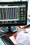 view of desk with computer monitor, stock info, papers, grocery list and notebook Stock Photo - Premium Rights-Managed, Artist: Andrew Kolb, Code: 700-06570972