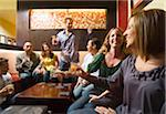 Men and women socializing in a bar in the city. Group of festive, smiling people celebrating with drinks. California USA Stock Photo - Premium Royalty-Free, Artist: Mitch Tobias, Code: 600-06571136