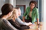Woman talking to team Stock Photo - Premium Royalty-Free, Artist: Westend61, Code: 6114-06589442