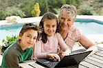 Woman and grandchildren with laptop Stock Photo - Premium Royalty-Free, Artist: Blend Images, Code: 6114-06589839