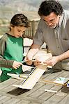 Boy and man making model aeroplane Stock Photo - Premium Royalty-Free, Artist: CulturaRM, Code: 6114-06589854