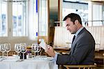 Businessman looking at menu Stock Photo - Premium Royalty-Freenull, Code: 6114-06590002