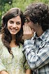 Man whispering to woman Stock Photo - Premium Royalty-Free, Artist: Blend Images, Code: 6114-06590110