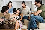 Man playing guitar for friends Stock Photo - Premium Royalty-Free, Artist: Blend Images, Code: 6114-06590122