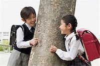 Boy and a girl next to a tree Stock Photo - Premium Royalty-Freenull, Code: 6114-06590433