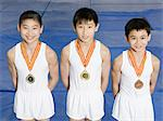 Young gymnasts with medals Stock Photo - Premium Royalty-Free, Artist: Blend Images, Code: 6114-06590488