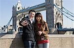 Couple taking picture by tower bridge Stock Photo - Premium Royalty-Freenull, Code: 6114-06590521