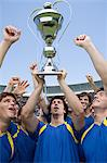 Footballers holding a trophy Stock Photo - Premium Royalty-Free, Artist: Ikon Images, Code: 6114-06590524