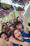 Footballers holding a trophy Stock Photo - Premium Royalty-Free, Artist: Blend Images, Code: 6114-06590536