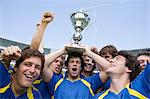 Footballers holding a trophy Stock Photo - Premium Royalty-Free, Artist: Blend Images, Code: 6114-06590540