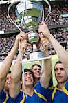 Footballers holding a trophy Stock Photo - Premium Royalty-Freenull, Code: 6114-06590542
