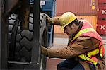 Man looking at truck tyre Stock Photo - Premium Royalty-Free, Artist: Blend Images, Code: 6114-06590764