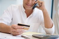 person on phone with credit card - A man telephone banking Stock Photo - Premium Royalty-Freenull, Code: 6114-06591096