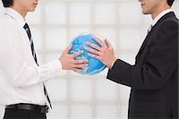 Office workers holding globe Stock Photo - Premium Royalty-Freenull, Code: 6114-06591186