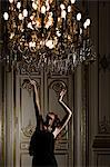 Woman dancing beneath chandelier Stock Photo - Premium Royalty-Free, Artist: Cultura RM, Code: 6114-06591295