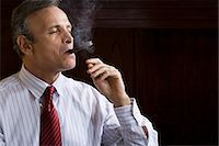Businessman smoking cigar Stock Photo - Premium Royalty-Freenull, Code: 6114-06591398