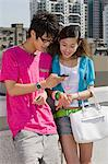 Teenage couple looking at cellphone Stock Photo - Premium Royalty-Free, Artist: Robert Harding Images, Code: 6114-06591585