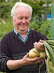 A gardener holding a bunch of onions Stock Photo - Premium Royalty-Free, Artist: Blend Images, Code: 6114-06591671