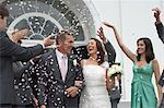 Guests throwing confetti over bride and groom Stock Photo - Premium Royalty-Free, Artist: Blend Images, Code: 6114-06591808