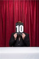 Judge with a score card covering his face Stock Photo - Premium Royalty-Freenull, Code: 6114-06591889