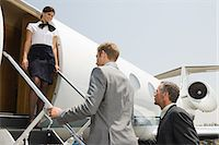 Stewardess and businessmen boarding jet Stock Photo - Premium Royalty-Freenull, Code: 6114-06592475