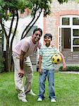 Father and son with football Stock Photo - Premium Royalty-Free, Artist: Blend Images, Code: 6114-06592505