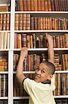 Boy at bookshelf Stock Photo - Premium Royalty-Free, Artist: Blend Images, Code: 6114-06593442