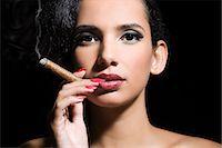 Woman smoking a cigar Stock Photo - Premium Royalty-Freenull, Code: 6114-06593598