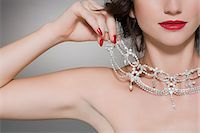 Woman trying on a diamond necklace Stock Photo - Premium Royalty-Freenull, Code: 6114-06593601