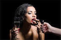 Woman lighting a cigar Stock Photo - Premium Royalty-Freenull, Code: 6114-06593625