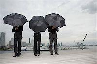 Businesspeople holding umbrellas Stock Photo - Premium Royalty-Freenull, Code: 6114-06594345