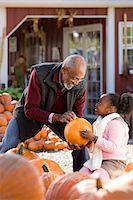 A man and his granddaughter choosing pumpkins Stock Photo - Premium Royalty-Freenull, Code: 6114-06594589