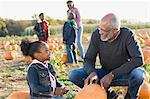 A grandfather and his granddaughter looking at pumpkins Stock Photo - Premium Royalty-Free, Artist: Cultura RM, Code: 6114-06594594