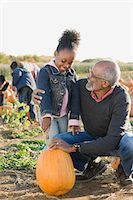 A grandfather and his granddaughter looking at pumpkins Stock Photo - Premium Royalty-Freenull, Code: 6114-06594607