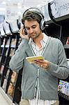 Man listening to music in supermarket Stock Photo - Premium Royalty-Freenull, Code: 6114-06594959