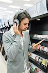 Man listening to music in supermarket Stock Photo - Premium Royalty-Freenull, Code: 6114-06594983