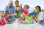 Little boy surrounded by clapping family, presents and colourful balloons Stock Photo - Premium Royalty-Freenull, Code: 6114-06595806