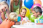 Little girls surrounded by family at her birthday party Stock Photo - Premium Royalty-Free, Artist: Blend Images, Code: 6114-06595857