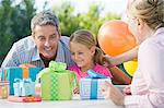 Little girl and her father looking at birthday presents Stock Photo - Premium Royalty-Free, Artist: Blend Images, Code: 6114-06595873