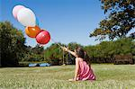 Little girls sitting on grass holding balloons Stock Photo - Premium Royalty-Free, Artist: Blend Images, Code: 6114-06596000
