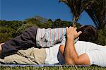 Little boy lying on father's tummy in the park Stock Photo - Premium Royalty-Free, Artist: Blend Images, Code: 6114-06596006