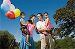 Family standing outside holding balloons Stock Photo - Premium Royalty-Free, Artist: Westend61, Code: 6114-06596015